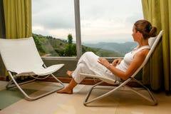 De vrouw zit in comfortabele leunstoel bij hotel hoog omhoog in bergen Stock Afbeeldingen
