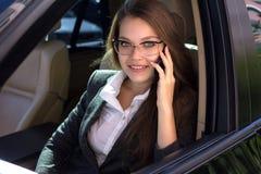 De vrouw zit in de auto en spreekt telefonisch Stock Fotografie