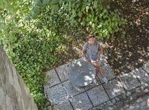De vrouw zit in de binnenplaats van Afgetapt Kasteel, Slovenië Royalty-vrije Stock Foto's