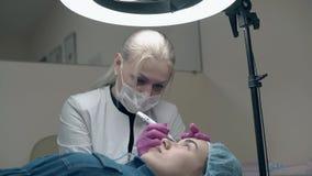 De vrouw zit dichtbij patiënt en past permanente samenstelling toe stock footage