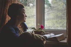 De vrouw zit door venster met opgesteld boek, denkt stock afbeeldingen