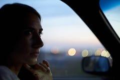 De vrouw zit in een auto op de achtergrond van stadslichten Avondnacht royalty-vrije stock fotografie
