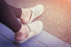 De vrouw zit gezet een voet op de vloer Royalty-vrije Stock Foto