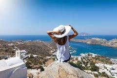 De vrouw zit hoog op een rots over het dorp van Ios eiland stock afbeelding
