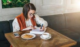 De vrouw zit in koffie bij lijst Het meisje vult een toepassing, vragenlijst, tekensdocumenten in, opstelt samenvatting royalty-vrije stock foto's