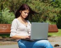 De vrouw zit met laptop computer op parkbank royalty-vrije stock afbeeldingen