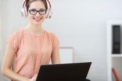 De vrouw zit met laptop op zijn aan muziek luisteren en overlapping die, die leren Het glimlachen van en het onderzoeken van de c Stock Foto