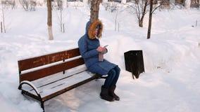 De vrouw zit op bank en het doorbladeren mobiele telefoon in de winterpark in de stad in de loop van de dag in sneeuwweer met stock videobeelden