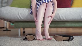 De vrouw zit op bank opstijgt hielen en betaalt massage stock video