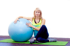 De vrouw zit op de bal in de gymnastiek Stock Afbeeldingen