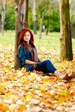 De vrouw zit op de herfstbladeren in een bos royalty-vrije stock afbeelding