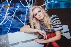 De vrouw zit op een bank in de winterweer Royalty-vrije Stock Afbeelding