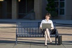 De vrouw zit op een Bank met haar Horizontaal Laptop - Royalty-vrije Stock Foto