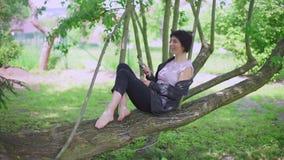 De vrouw zit op een boom, gebruikt de telefoon stock footage