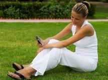 De vrouw zit op een gazon stock fotografie