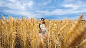 De vrouw zit op een gebied van tarwe en geniet van aard Royalty-vrije Stock Foto