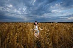 De vrouw zit op een gebied van tarwe en geniet van aard Stock Afbeeldingen