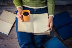 De vrouw zit op een houten vloer en leest een boek terwijl het houden van een koffiekop stock foto