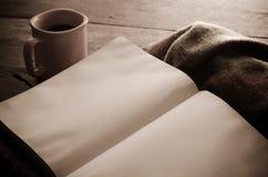 De vrouw zit op een houten vloer en leest een boek terwijl het houden van een koffiekop stock afbeelding