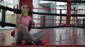 De vrouw zit op een mat en drinkt water van fles na een sporten opleiding stock videobeelden