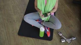 De vrouw zit op een mat met domoren en luistert aan muziek op hoofdtelefoons stock video