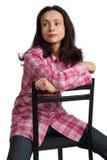De vrouw zit op een stoel terug naar voorzijde. royalty-vrije stock afbeelding