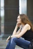 De vrouw zit op trede vooruit kijkt Royalty-vrije Stock Foto