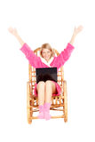 De vrouw zit in schommelstoel met omhoog handen stock afbeeldingen