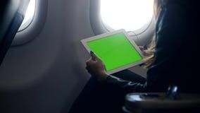 De vrouw zit tijdens de vlucht bij vliegtuig en het luisteren favoriet lied in hoofdtelefoon voor vermaak stock footage