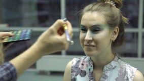 De vrouw zit voor visagiste, proces van make-up stock video