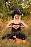 De vrouw in de zitting van het heksenkostuum in lotusbloem stelt Stock Foto