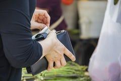 De vrouw in zwarte bovenkant die Amerikaanse dollars trekken van zippered beurs voor aankoop bij landbouwersmarkt met vage eracht royalty-vrije stock afbeelding