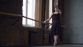 De vrouw in zwarte kleding maakt balletbeweging dichtbij venster in balzaal stock videobeelden