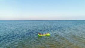 De vrouw zwemt in het overzees op motras stock videobeelden
