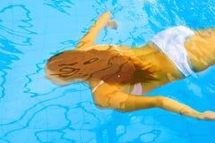 De vrouw zwemt onderwater Stock Foto