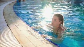 De vrouw zwemt in openlucht in de pool met blauw transparant water in de zonnige dag die, een zwembad, water ontspannen stock videobeelden