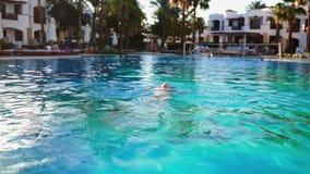De vrouw zwemt in openlucht in de pool met blauw transparant water in de zonnige dag die, een zwembad, water ontspannen stock video