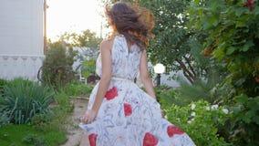De vrouwelijke aantrekkelijkheid, blootvoetse vrouw in lange kleding wenkt en loopt langs weg onder bloemen stock videobeelden