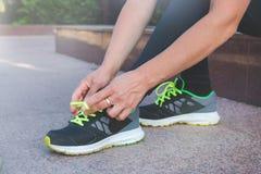 De vrouwelijke agent die haar schoenen binden voorbereidingen treffend voor een looppas stoot buiten aan stock fotografie