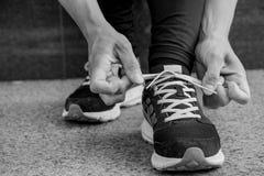 De vrouwelijke agent die haar schoenen binden voorbereidingen treffend voor een looppas stoot buiten zwart-wit beeld aan stock foto