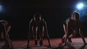 De vrouwelijke agenten bij atletiek volgen het buigen bij de startblokken vóór een ras in langzame motie stock footage