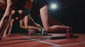 De vrouwelijke agenten bij atletiek volgen het buigen bij de startblokken vóór een ras in langzame motie stock videobeelden