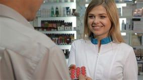 De vrouwelijke apotheker biedt ruiten aan de cliënt aan bij de drogisterij stock video