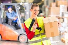 De arbeider houdt pakket in pakhuis van het door:sturen Stock Afbeeldingen