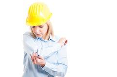 De vrouwelijke architect die helm dragen die haar elleboog controleren verwondt Royalty-vrije Stock Foto
