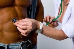 De vrouwelijke arts controleert een patiënt stock afbeeldingen
