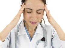 De vrouwelijke arts of de verpleegster werkte zich en hebben hoofdpijn over stock afbeeldingen