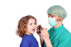 De vrouwelijke arts geeft een meisje een behandeling Stock Fotografie