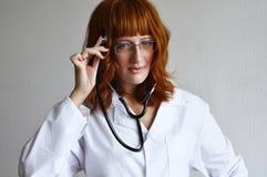 De vrouwelijke arts luistert aan haar gedachten Royalty-vrije Stock Afbeeldingen
