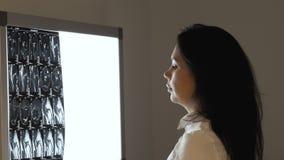 De vrouwelijke arts onderzoekt het beeld van de magnetische resonantietomografie bij het scherm stock videobeelden